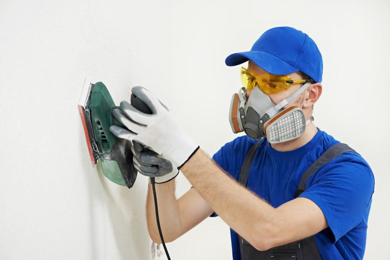 photodune-3980978-worker-with-orbital-sander-at-wall-filling-m