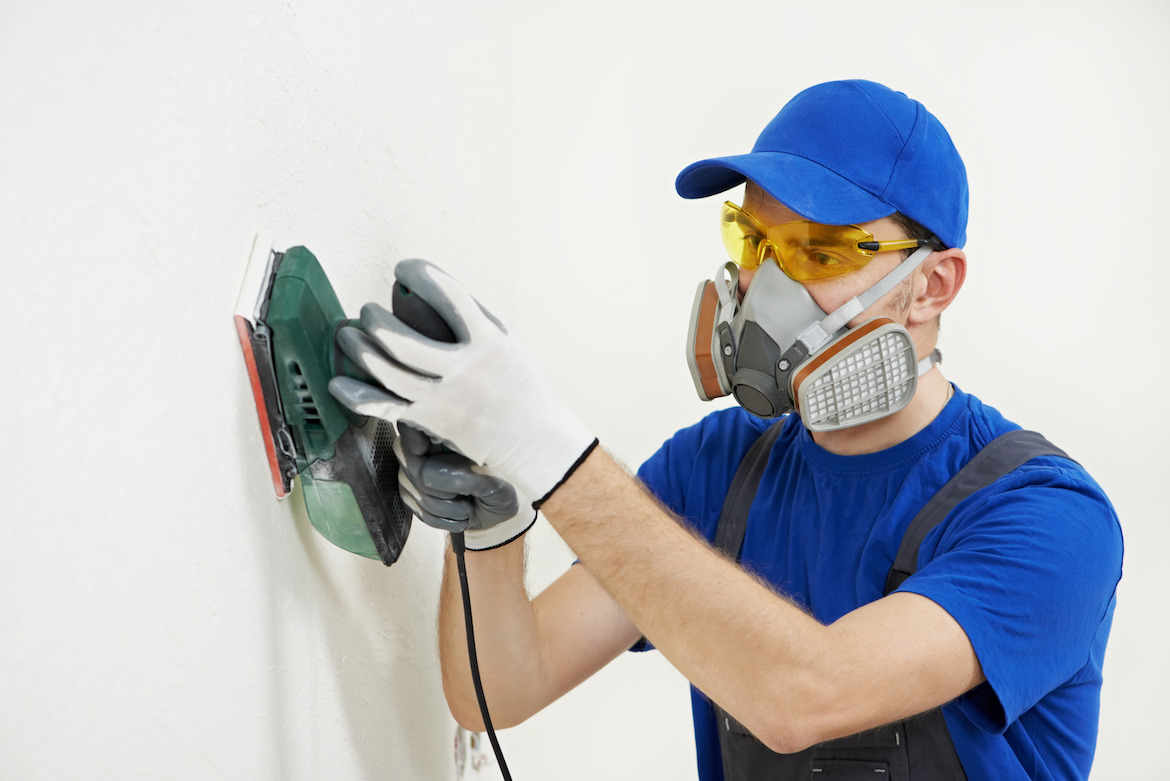 photodune-3980978-worker-with-orbital-sander-at-wall-filling-m